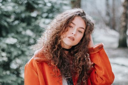 curly haired woman in a red coat